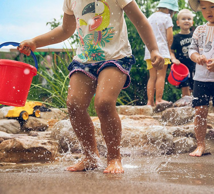 Child jumping in puddle at new childcare centre in Ocean Grove